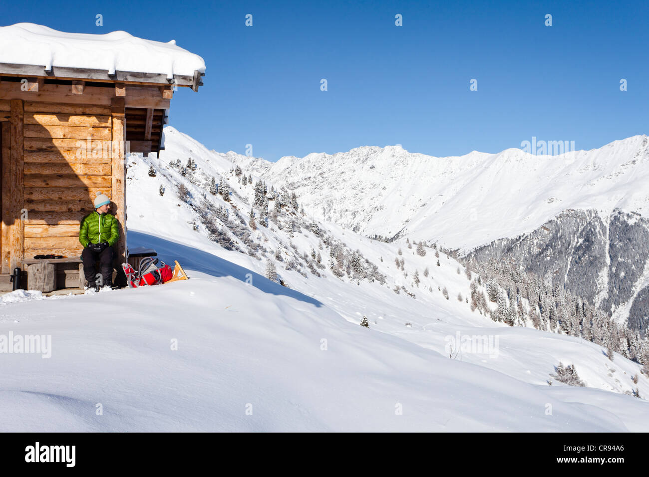 Snowshoer resting at Jagelealm alpine pasture above Entholz, overlooking the Ridnauntal Valley, Alto Adige, Italy, - Stock Image