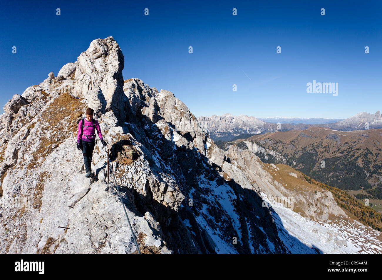 Hiker on Bepi Zac climbing route in the San Pellegrino Valley above the San Pellegrino Pass, with the Dolomites Stock Photo