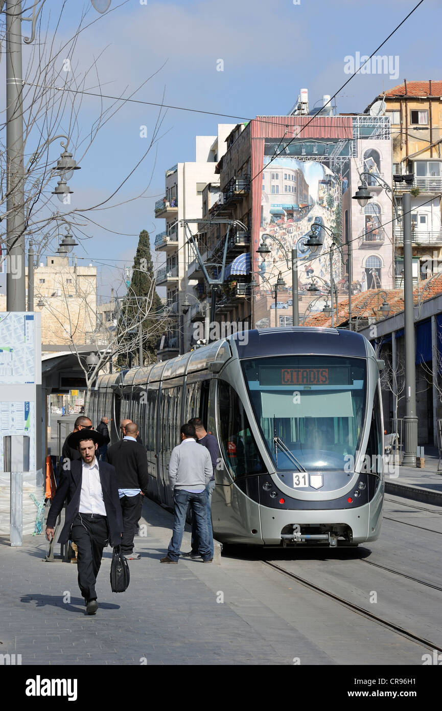 Street scene on the Jaffa Road with Orthodox Jews and a tram of the new tram line, light rail, and a mural of the - Stock Image
