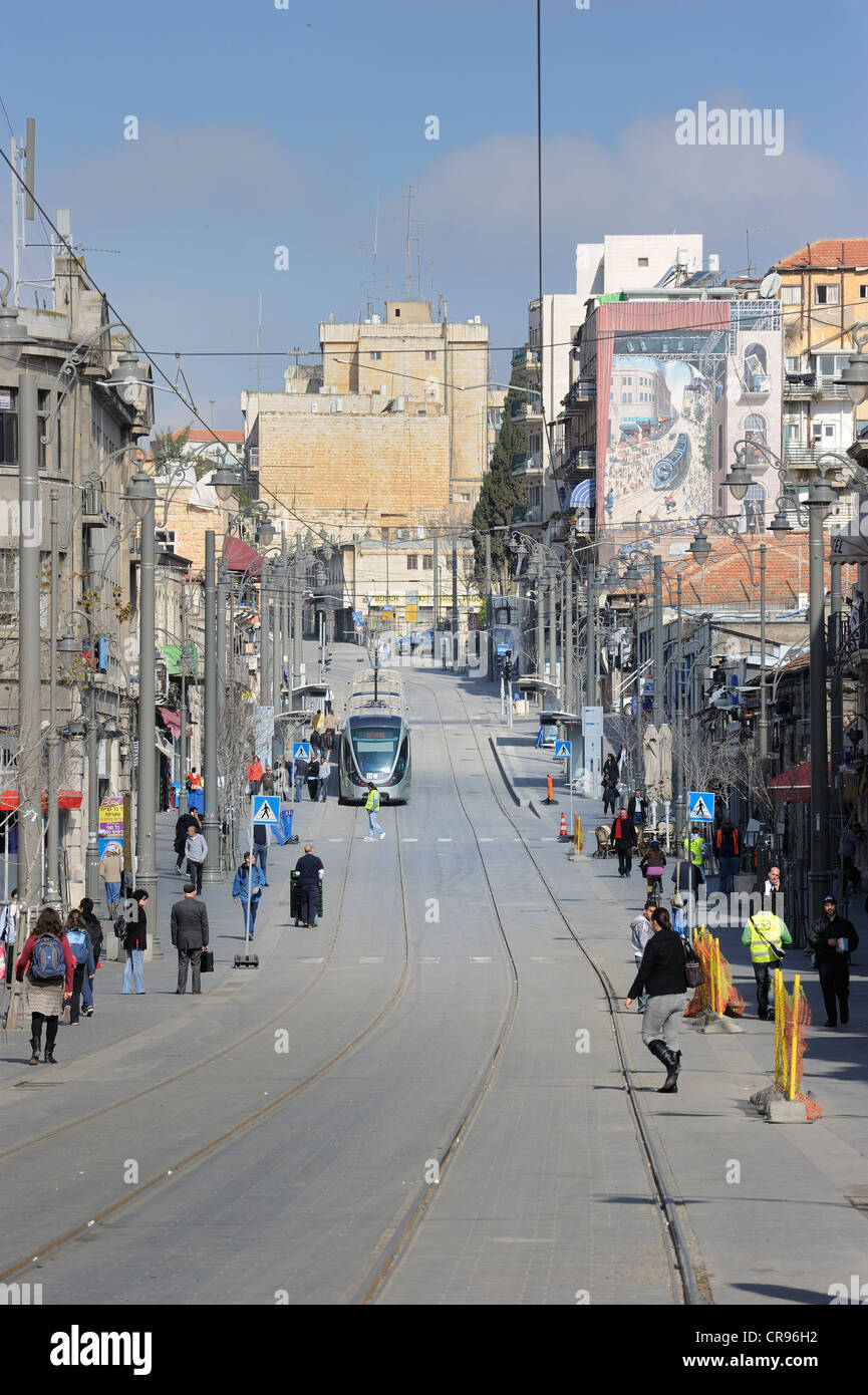 Street scene on the Jaffa Road with Orthodox Jews and the rails of the new tram line, light rail, and a mural of - Stock Image