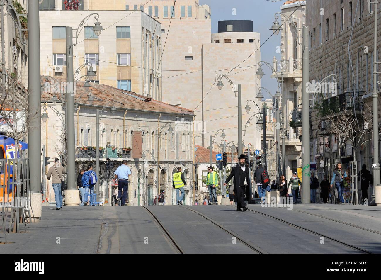 Street scene on the Jaffa Road with Orthodox Jews and the rails of the new tram line, light rail, Jerusalem, Israel, - Stock Image