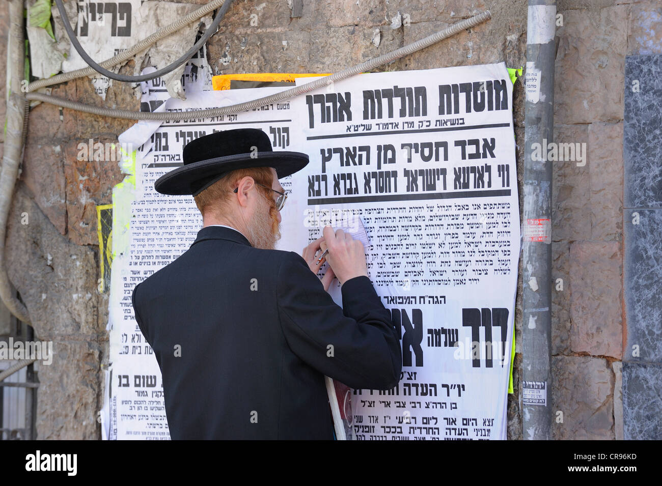 Street scene with an Orthodox Jew in the Me'a She'arim district, with typical wall newspapers, Jerusalem, - Stock Image