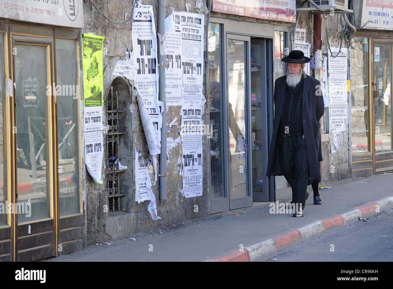 Street scene with an Orthodox Jew and typical wall newspapers in the district of Me'a She'arim or Mea Shearim, - Stock Image