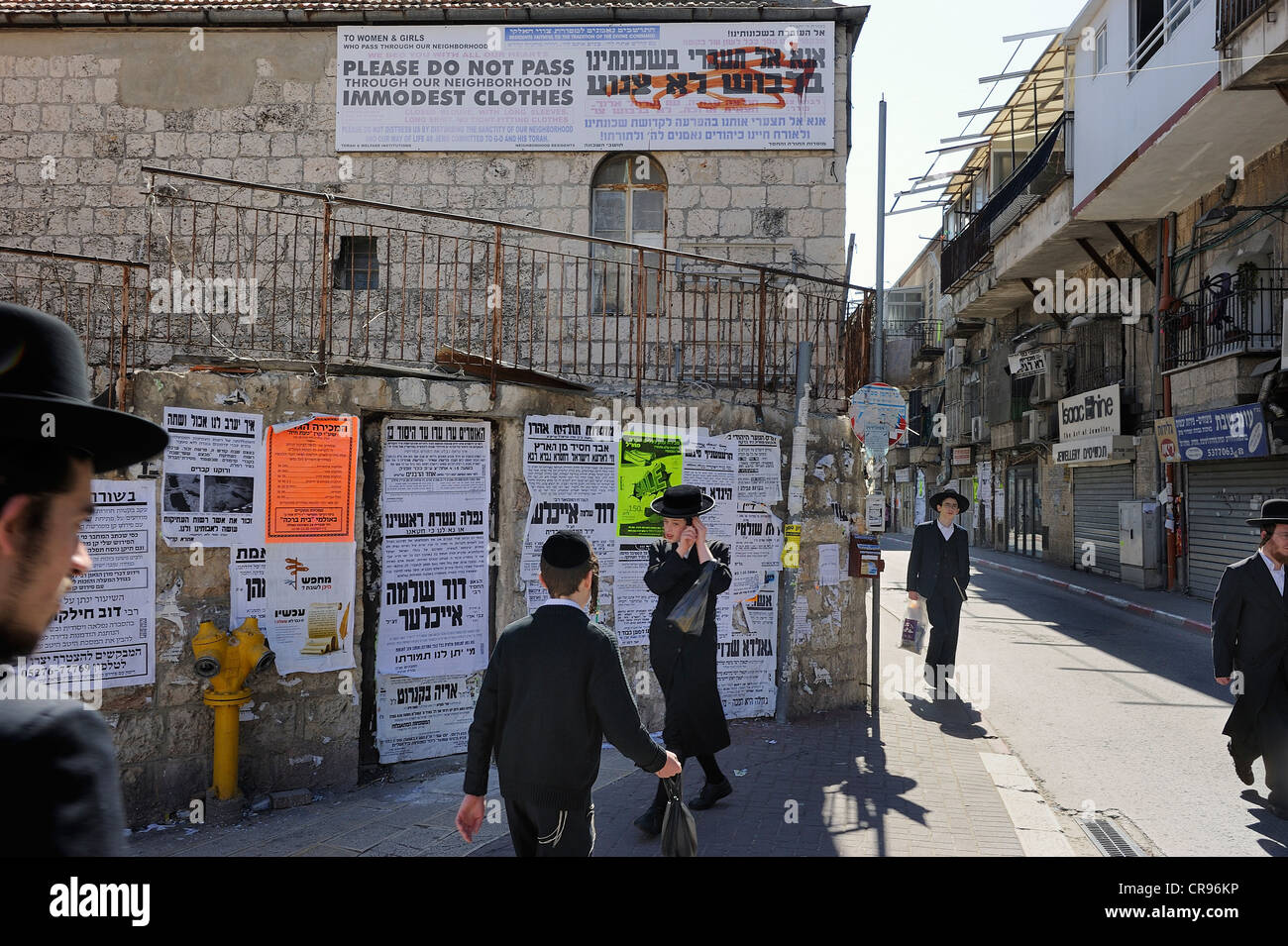 Banner up on a house with rules of conduct for tourists, wall newspapers and Orthodox Jews at the front in the district - Stock Image