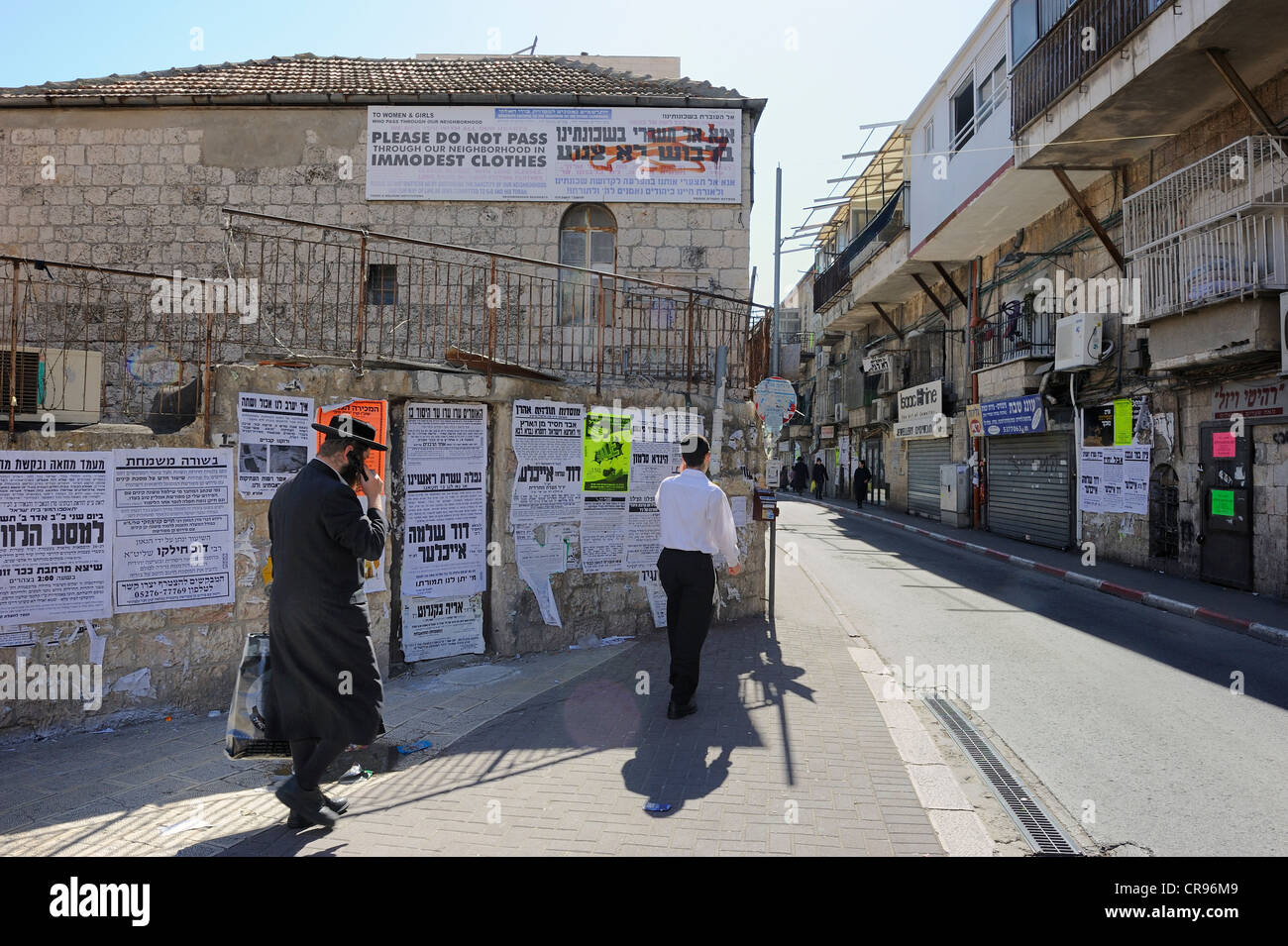 Banner up on a house with rules of conduct for tourists, wall newspapers and an Orthodox Jew with a mobile phone - Stock Image