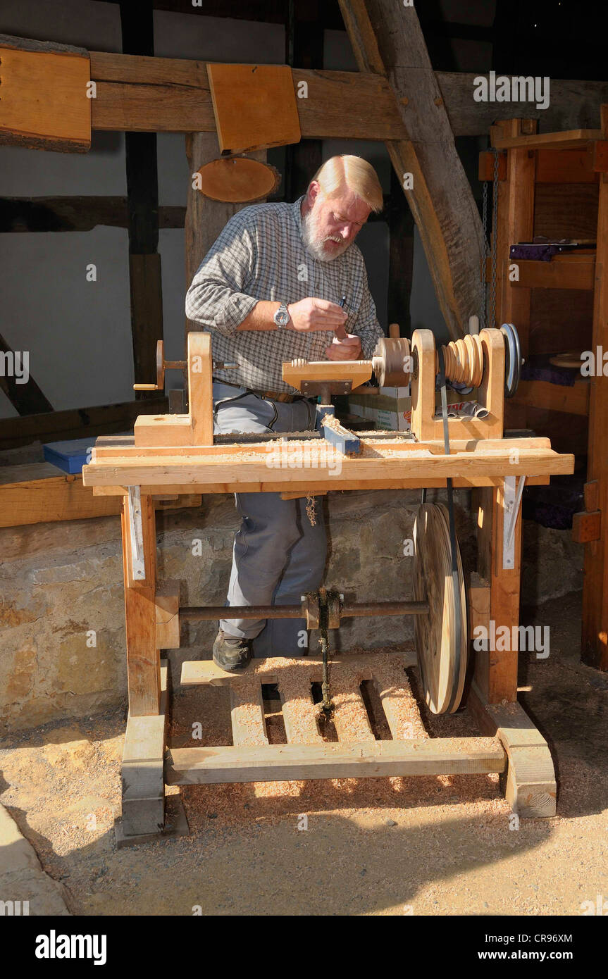 Turner working on a foot powered lathe, Hessenpark outdoor museum near Neu-Anspach, Hochtaunuskreis district, Hesse - Stock Image
