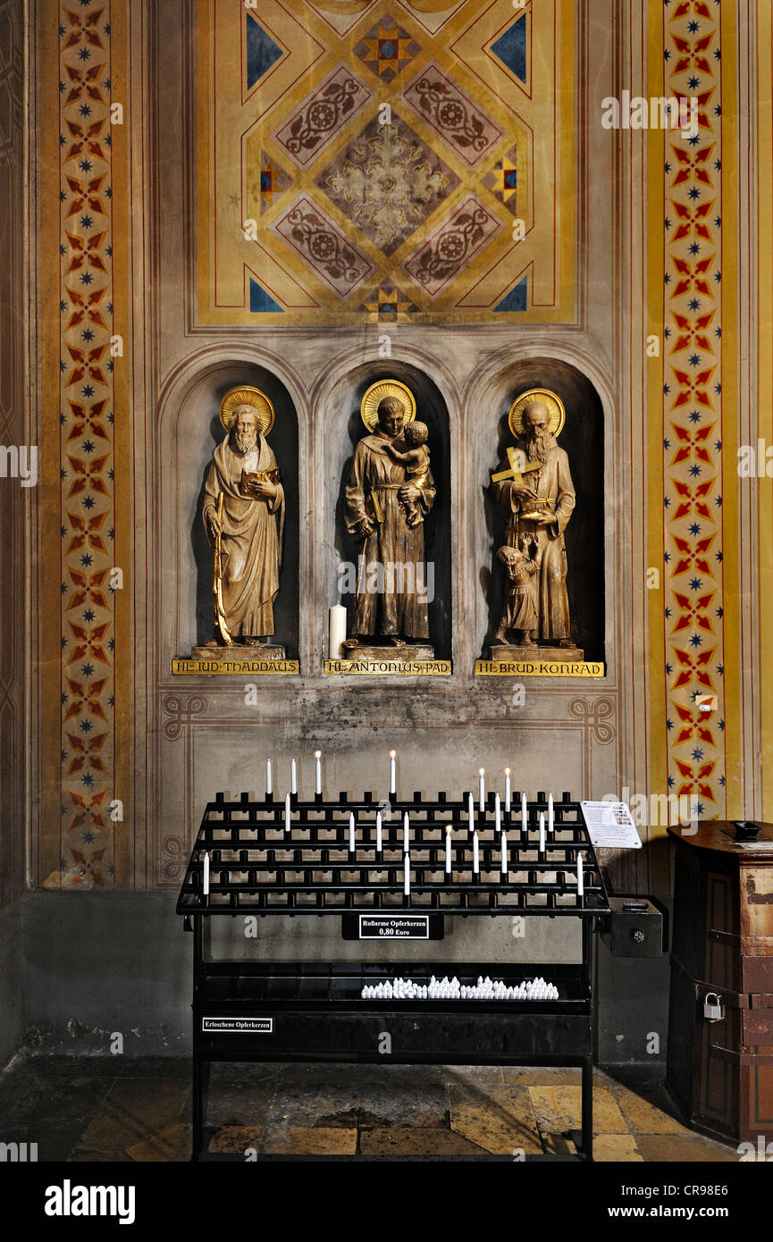 Ludwigskirche, St. Louis Church, three statues of saints and candles emitting little soot, Munich, Bavaria, Germany, - Stock Image
