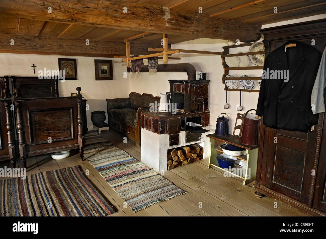Bedroom with a tiled stove, Bernoeder Hof farmhouse, Bauernhausmuseum Amerang farmhouse museum, Amerang, Bavaria - Stock Image