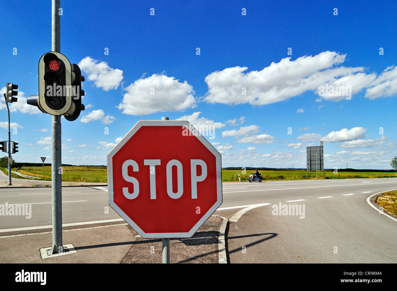 Stop sign and traffic lights, blue sky with fleecy clouds, Garching near Munich, Bavaria, Germany, Europe - Stock Image