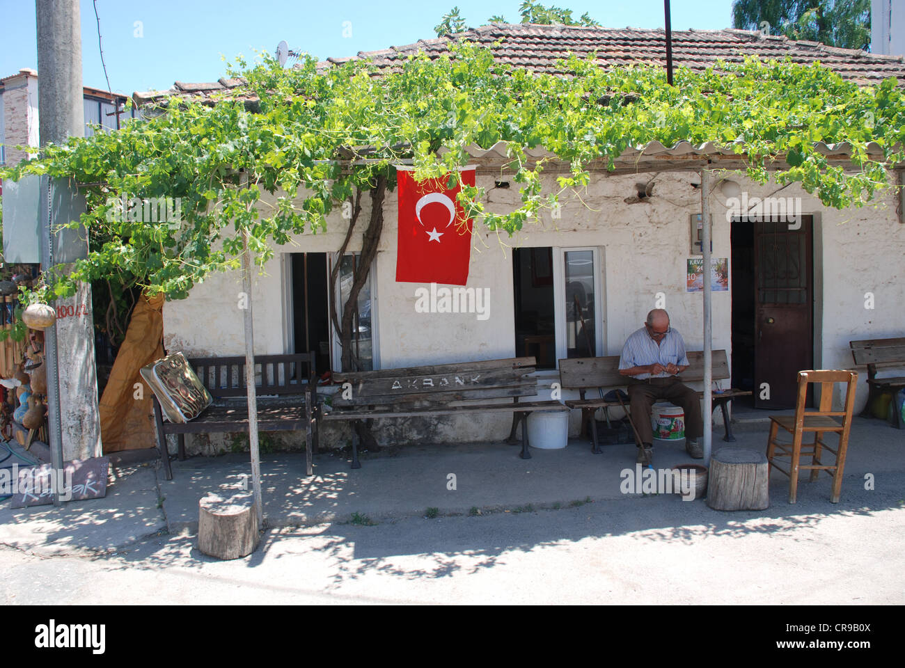 An elderly man in the town of Gumusluk underneath the national flag in South West Turkey. Picture by: Adam Alexander/Alamy - Stock Image