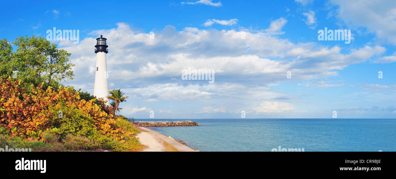 Cape Florida Light lighthouse with Atlantic Ocean and palm tree at beach in Miami with blue sky and cloud. - Stock Image