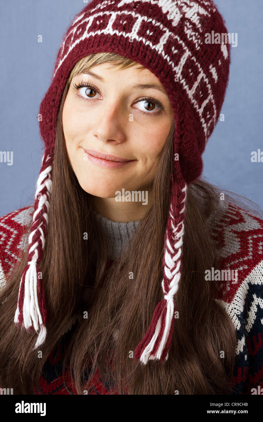 3505fa7d144b Pretty young woman with a slight smile wearing wool cap with norwegian  pattern. Studio portrait against a light blue background