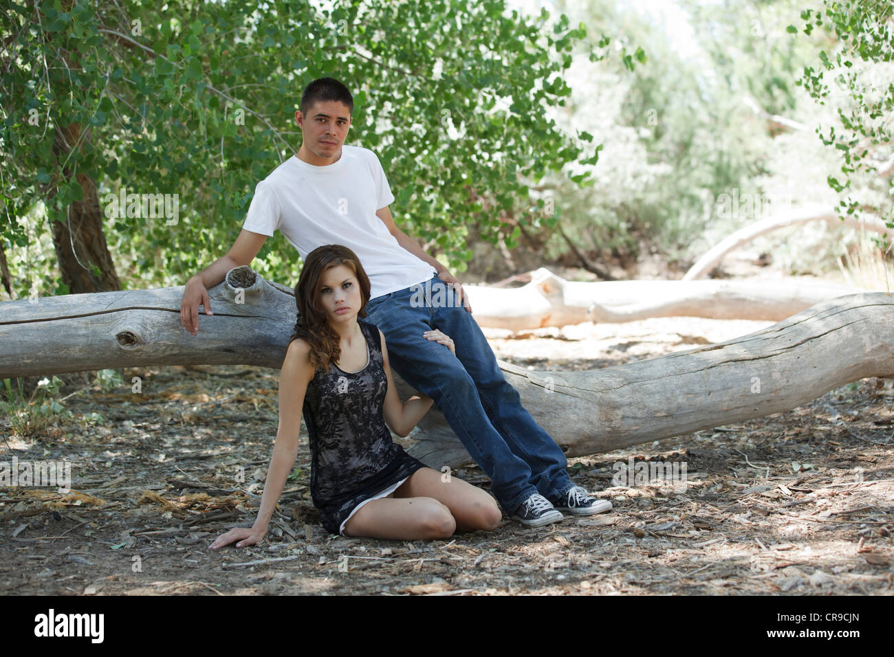 Beautiful young couple sitting out in the woods. She is on the ground, leaning on his leg, he is sitting on a log, Stock Photo