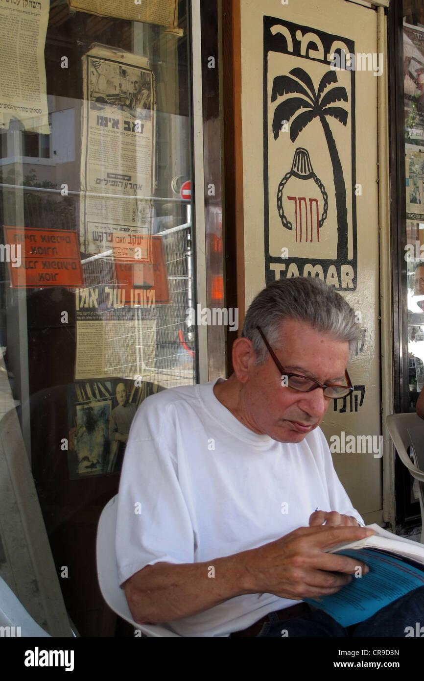 A man reading a book in Tamar coffeehouse in Shenkin street Tel Aviv Israel Stock Photo