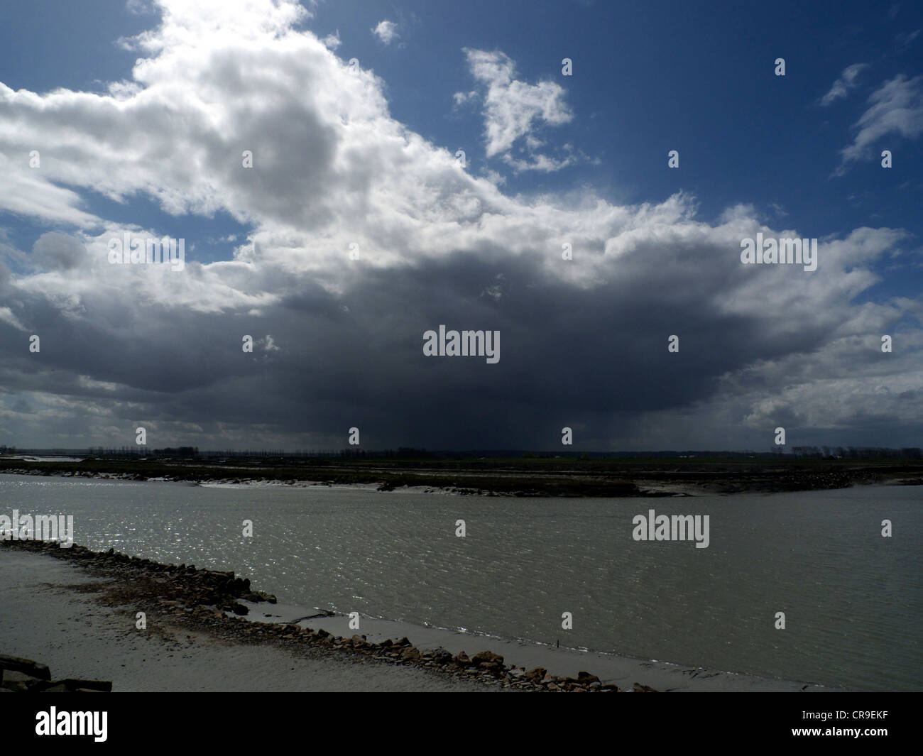 Black storm cloud with silvery lining, sun and blue sky, shoreline. - Stock Image