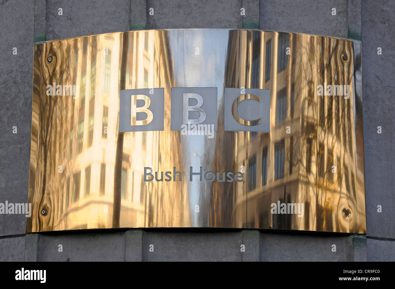 Brass BBC name plate & reflections on curved surface outside of the Bush House headquarters building for BBC World Stock Photo