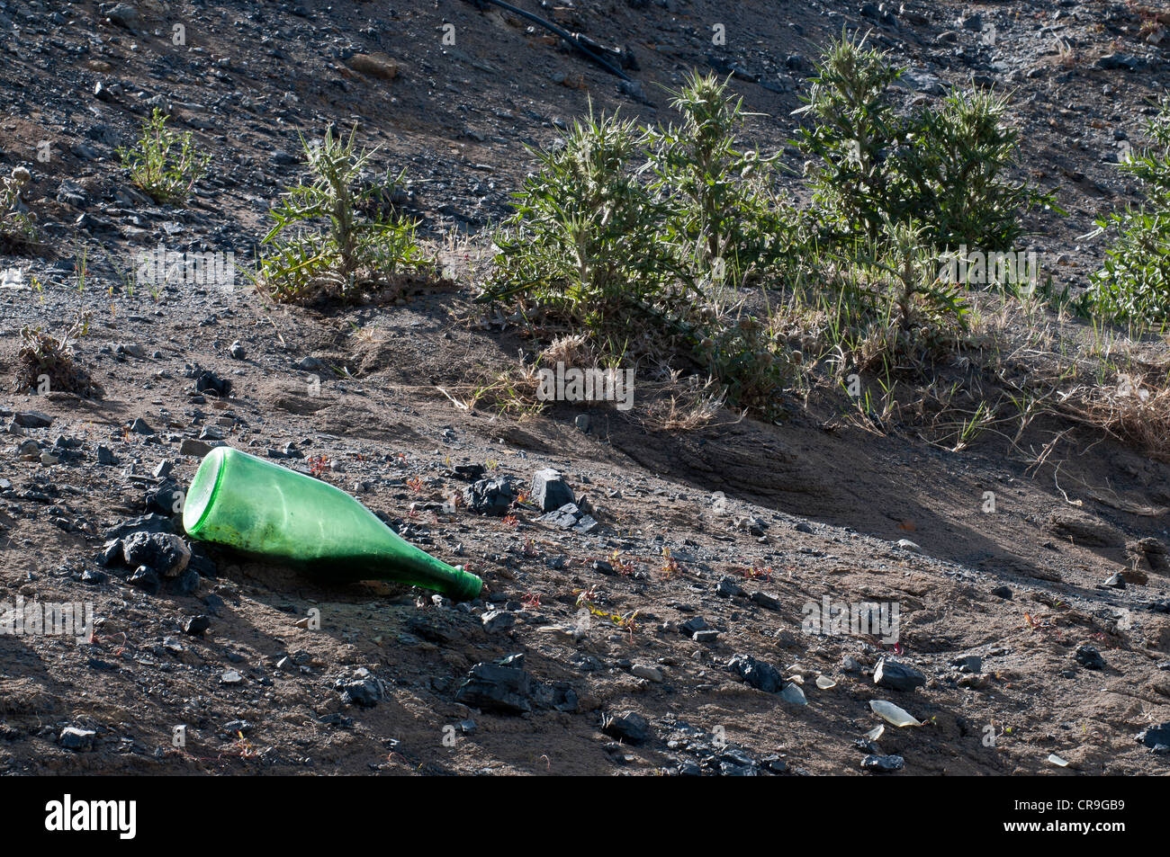 Wasteland with discarded bottle backlit Yacimientos Carboniferos de Rio Turbio Coal Mine Santa Cruz Province Patagonia - Stock Image