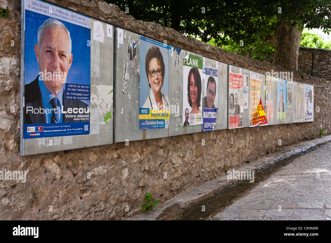 A wall of posters of candidates for the French parliamentary elections 2012 in the village of Saint-Guilhem-le-Désert, - Stock Image