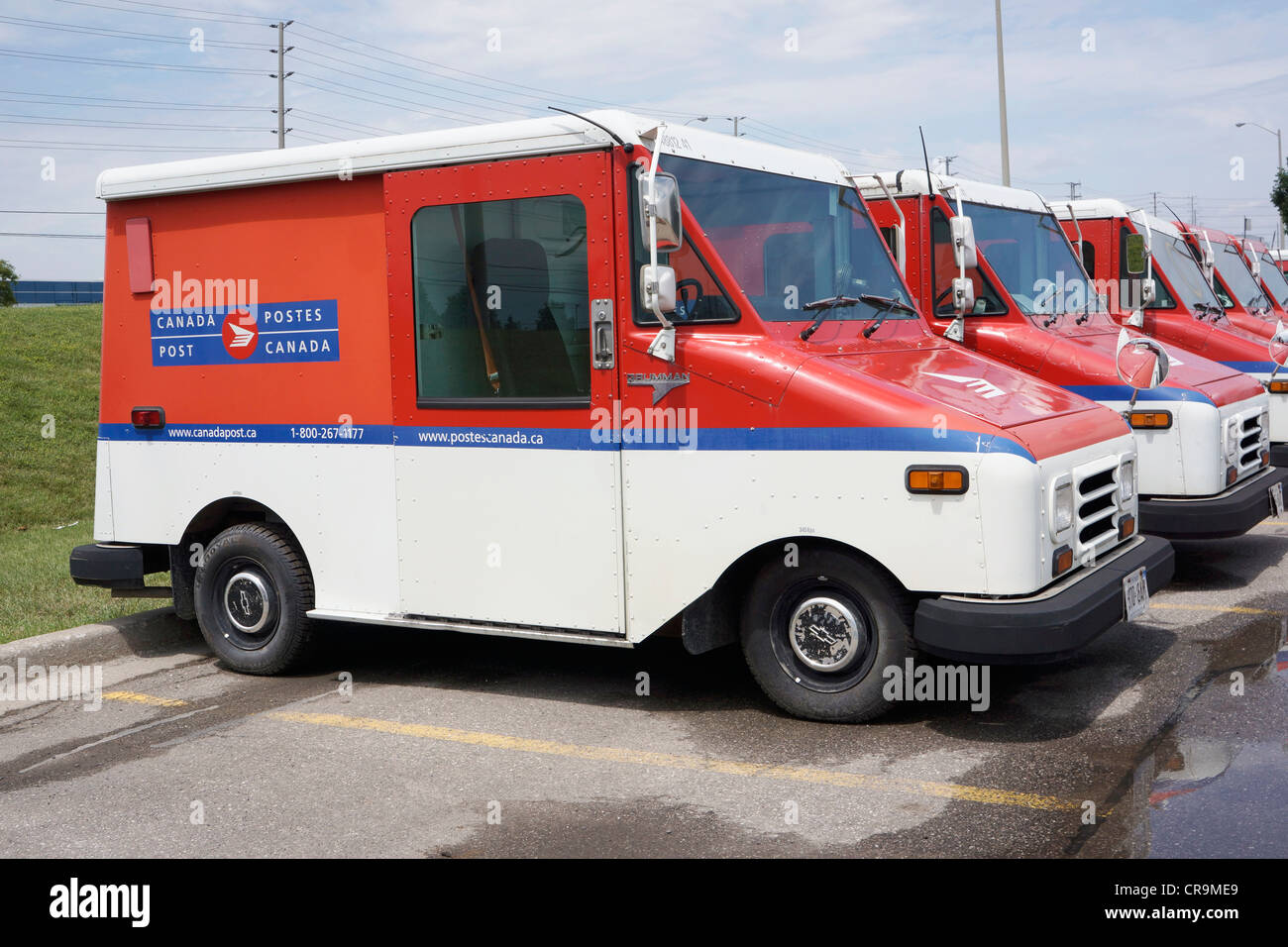Canada Post Vans, parked outside in a row - Stock Image