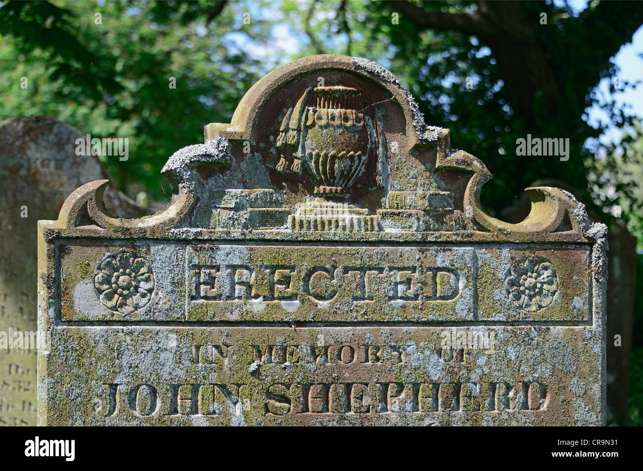 Gravestone with urn, books and lichen. Church of Saint Mary. Gosforth. Lake District National Park, Cumbria, England, - Stock Image