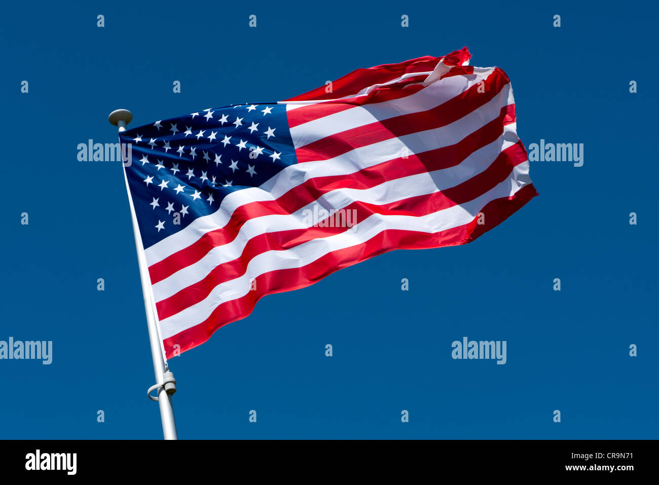 The American flag fluttering atop a flagpole Stock Photo