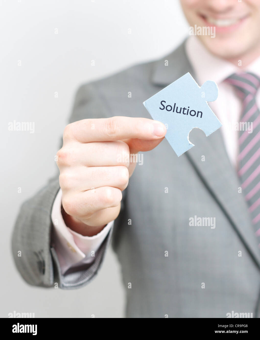 A business man solving a puzzle - Stock Image