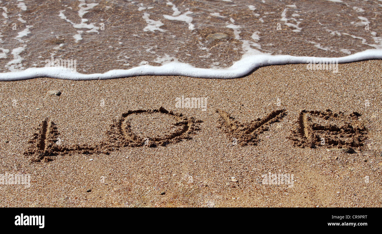 Stock Photo - The word 'love' written on the sand - Stock Image