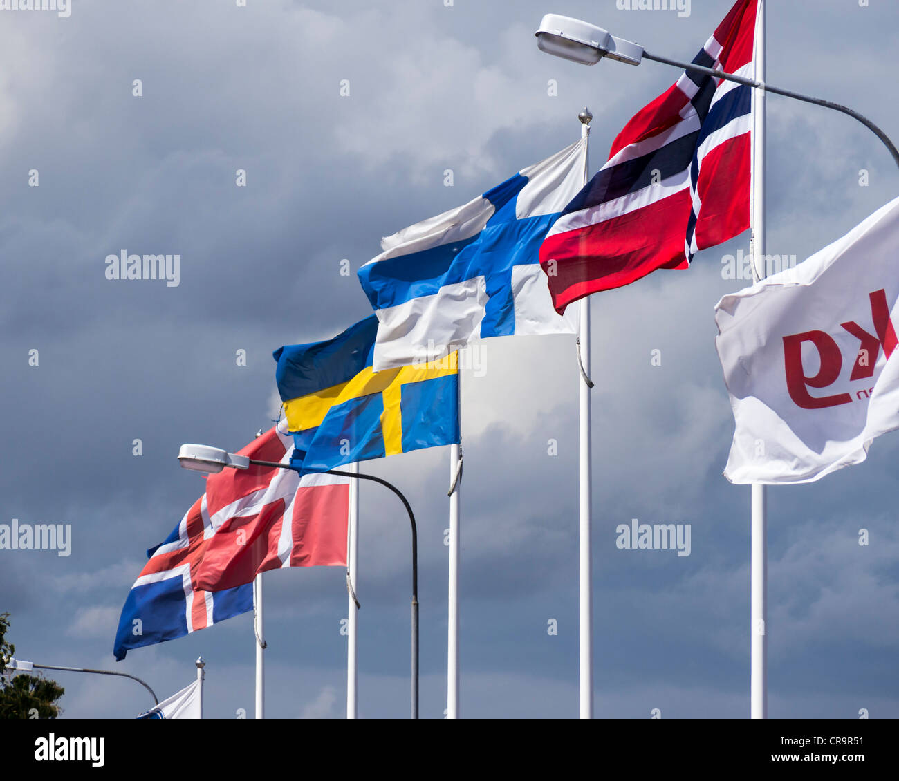 Flags of the nordic countries (from left to right Iceland, Denmark, Sweden, Finland and Norway) fly in the harbour - Stock Image