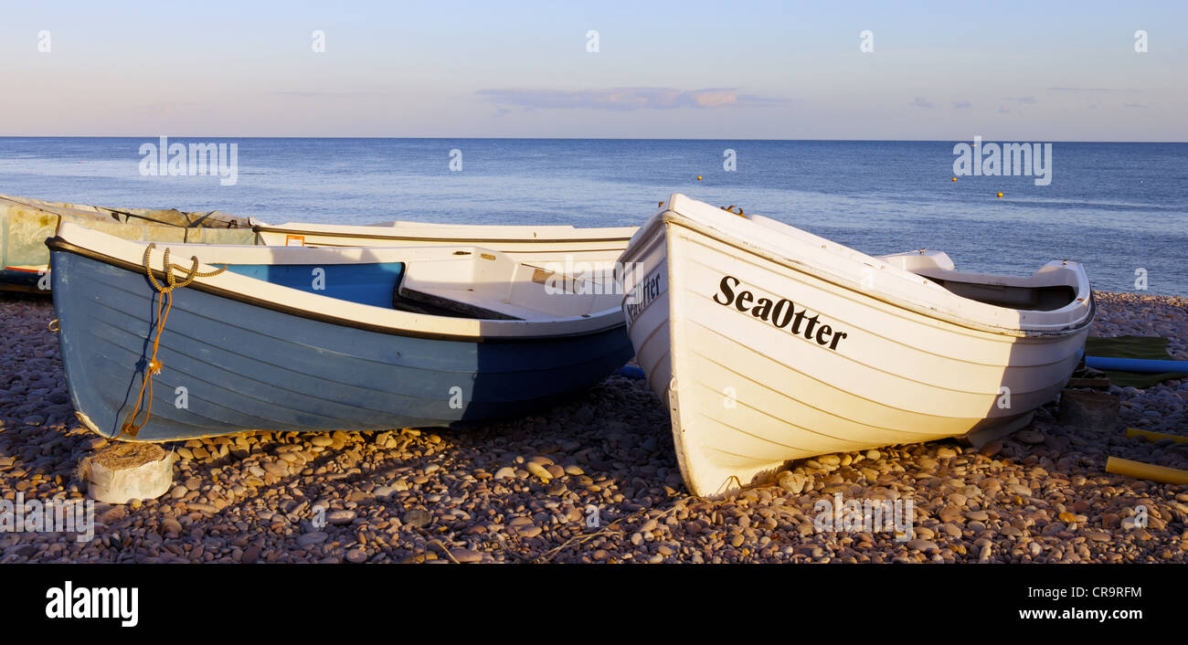 "The small boat ""Seaotter"" is bathed in sunshine on Budleigh Salterton beach, East Devon, as sunset. Stock Photo"