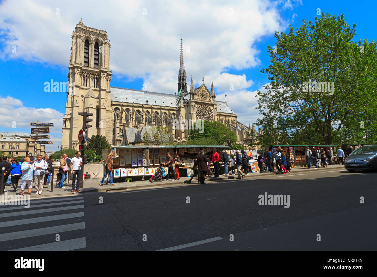 Left Bank, Paris, with Notre Dame Cathedral. Tourists look at vendors kiosks on a sunny spring afternoon - Stock Image