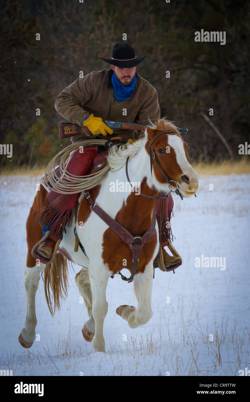 Cowboy and his horse riding through the snow on a ranch in northeastern Wyoming - Stock Image