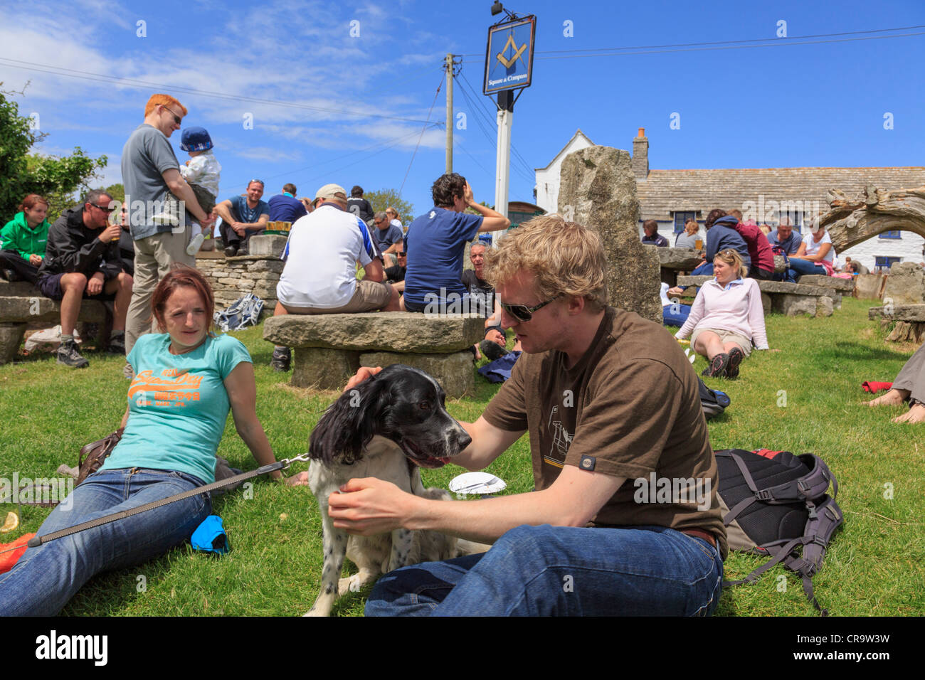 Everyday scene with people sitting in busy beer garden of Square and Compass country village pub lifestyle in summer - Stock Image