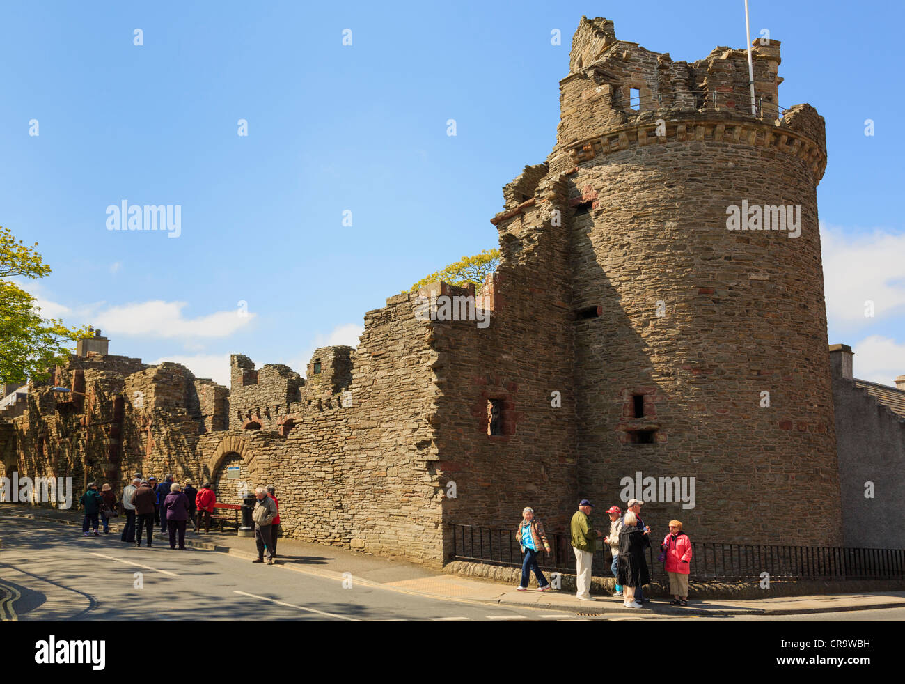 Tourists by remains of round tower or Moosie Toor and 12thc Bishop's Palace ruins in Kirkwall, Orkney Islands, - Stock Image