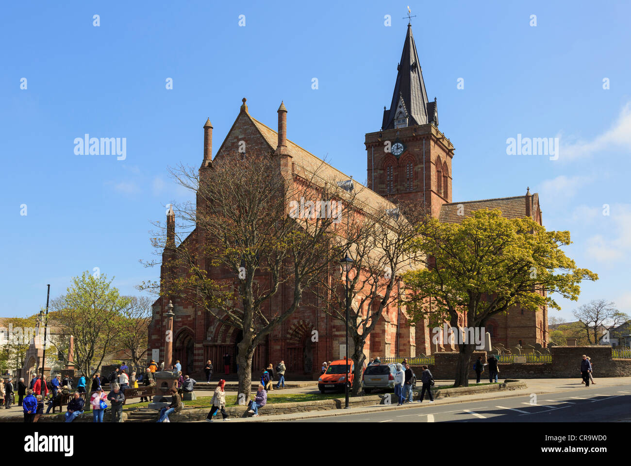Street scene at Kirk Green with trees growing outside St Magnus cathedral busy with tourists Kirkwall Orkney Mainland - Stock Image