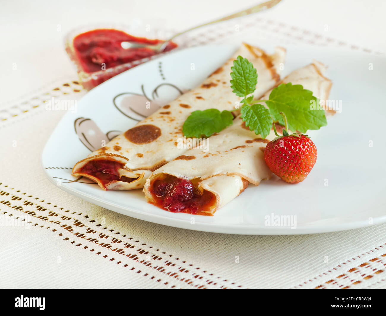 Rolled pancakes with strawberries - Stock Image