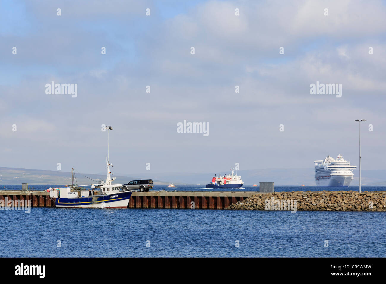 Large cruise liner Caribbean Princess moored outside harbour wall whilst visiting Orkneys. Kirkwall, Orkney Islands, - Stock Image