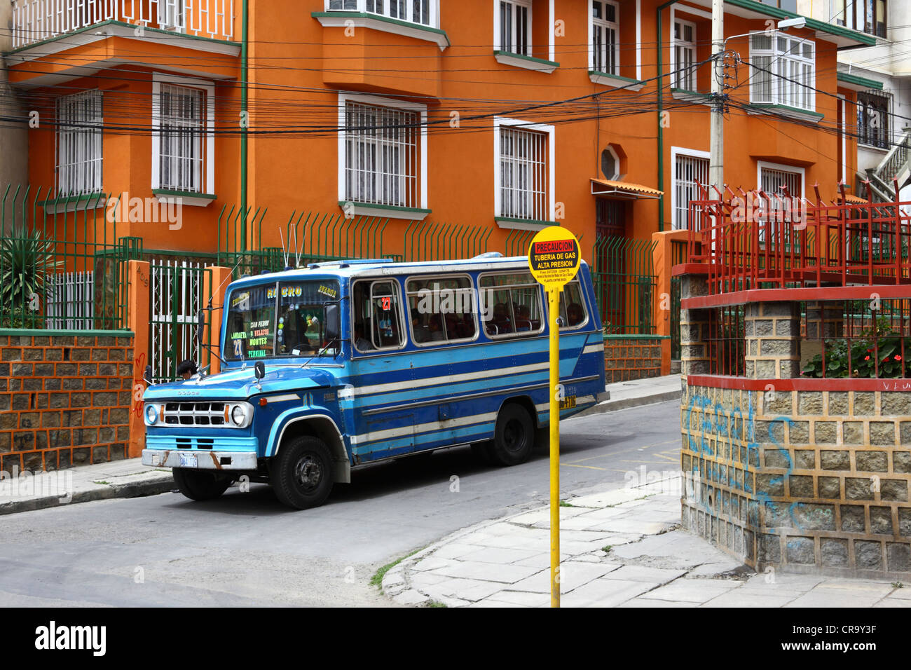 Micro public bus passing sign warning of underground domestic gas supply pipeline in a residential suburb, La Paz, - Stock Image