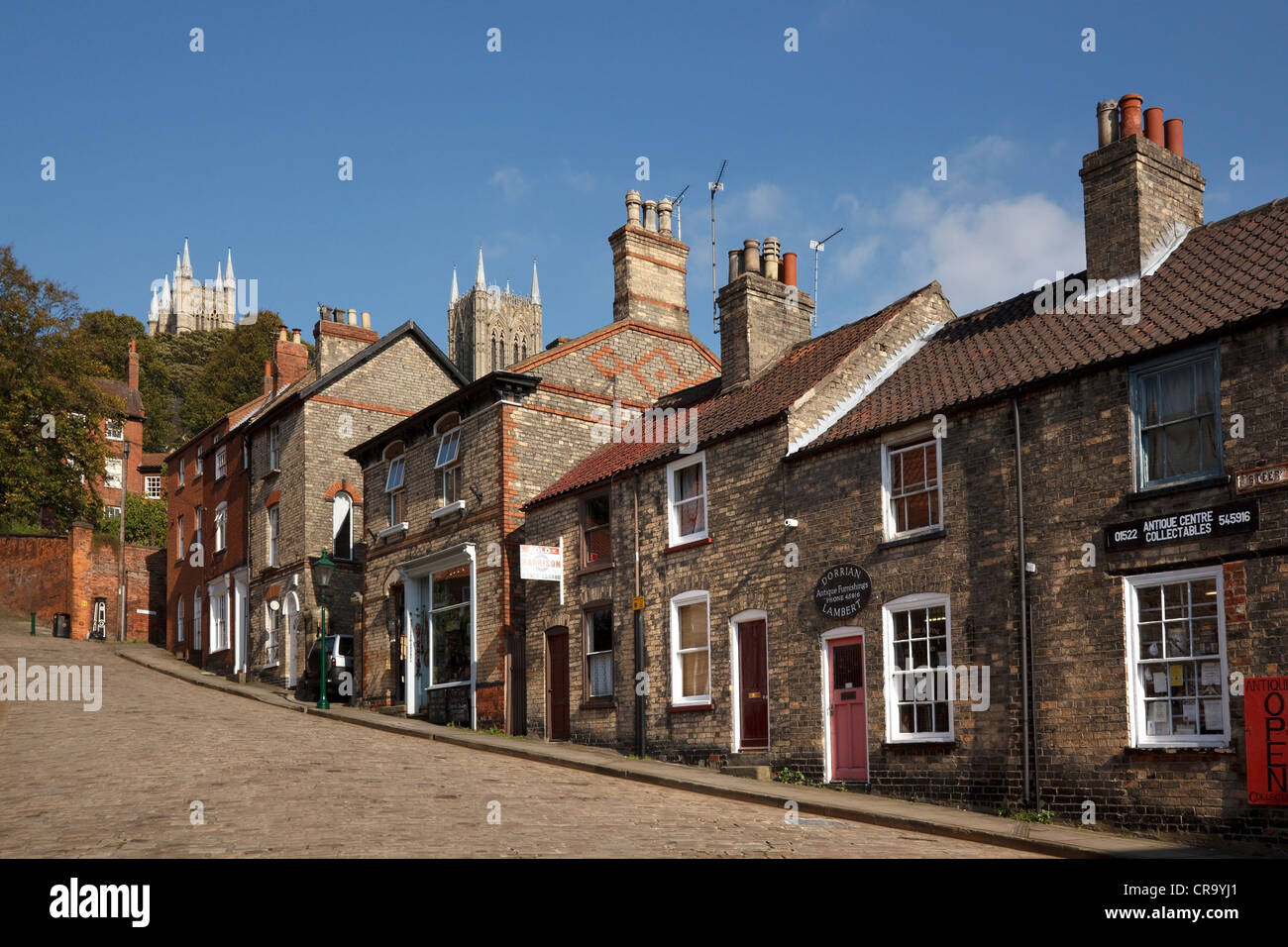 Old traditional terraced shop fronts and houses on cobbled street, Steep Hill, Lincoln, Lincolnshire, England, UK - Stock Image