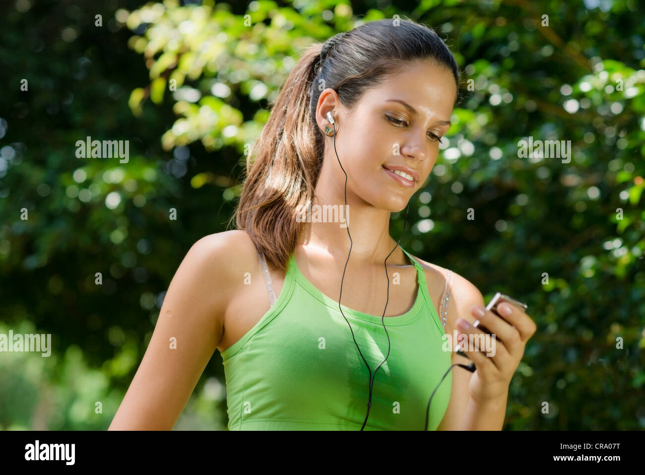 Young woman with mp3 player doing fitness in city park Stock Photo