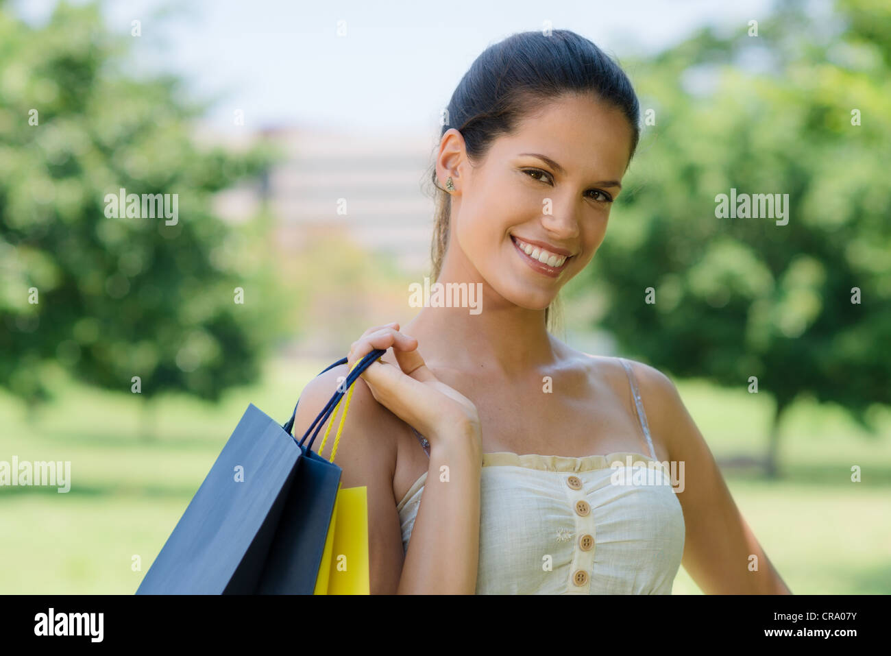 Consumerism, portrait of happy young woman smiling with shopping bags - Stock Image
