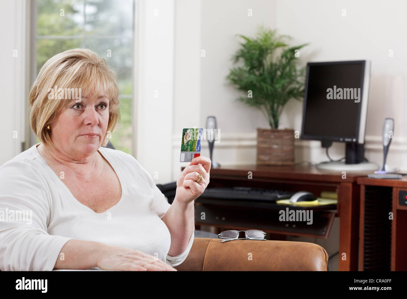 Mature woman holds a credit card and stares intently - Stock Image