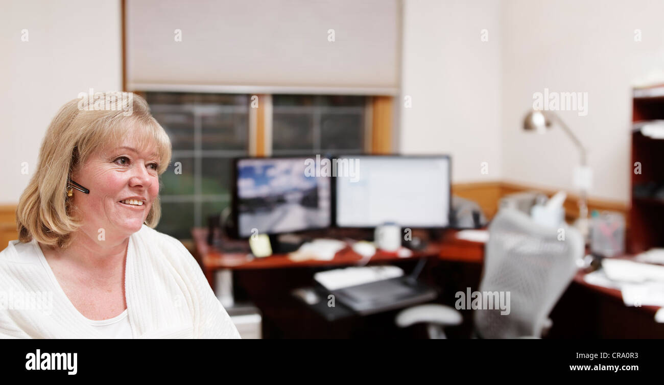 Mature woman in her home office - Stock Image