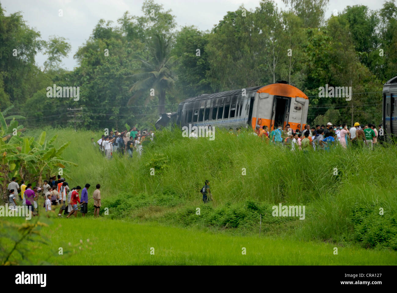 More and more onlookers arriving to see the burnt out train on the 14/06/2011 in Phitsanulok Thailand - Stock Image