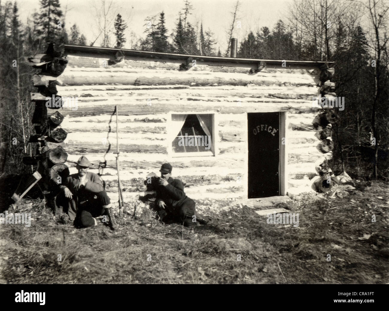 Two Men at Crude Log Cabin Office - Stock Image