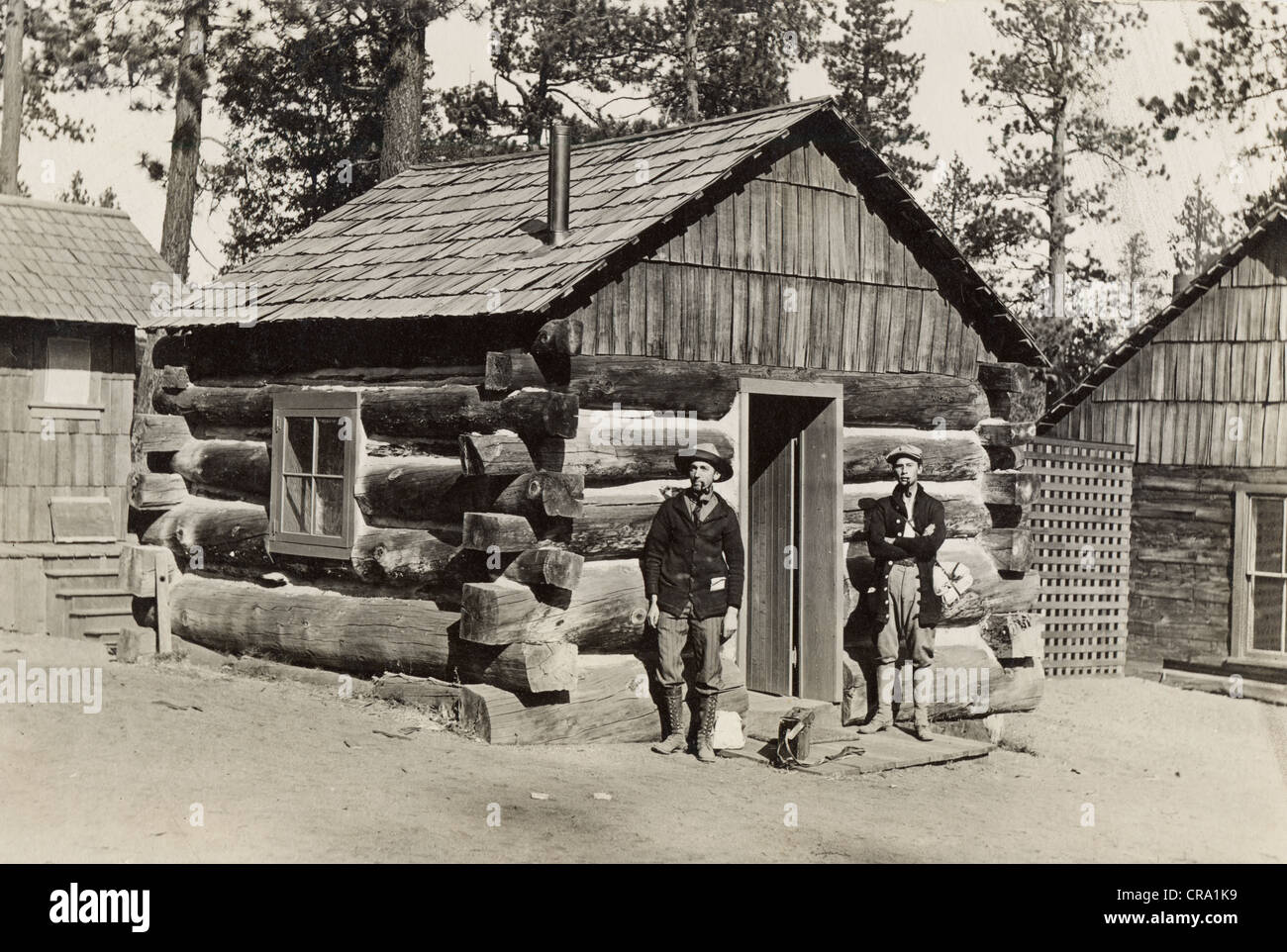 Father & Son in front of Small Log Cabin - Stock Image