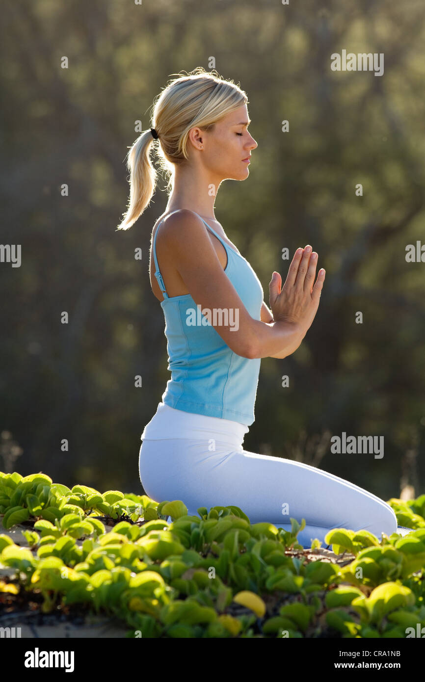 Woman practices yoga at Makena, Maui, Hawaii. - Stock Image