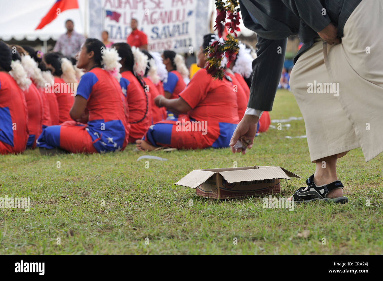 Guests come forward and contribute money into a cardboard box for performers at celebrations of Samoa's 50 years - Stock Image