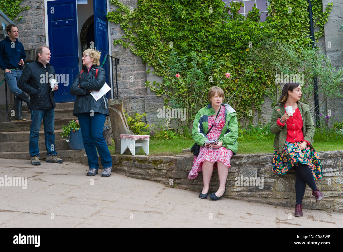 People relaxing outside HowTheLightGetsIn, the philosophy and music festival at Globe at Hay, Hay-on-Wye, Powys, - Stock Image