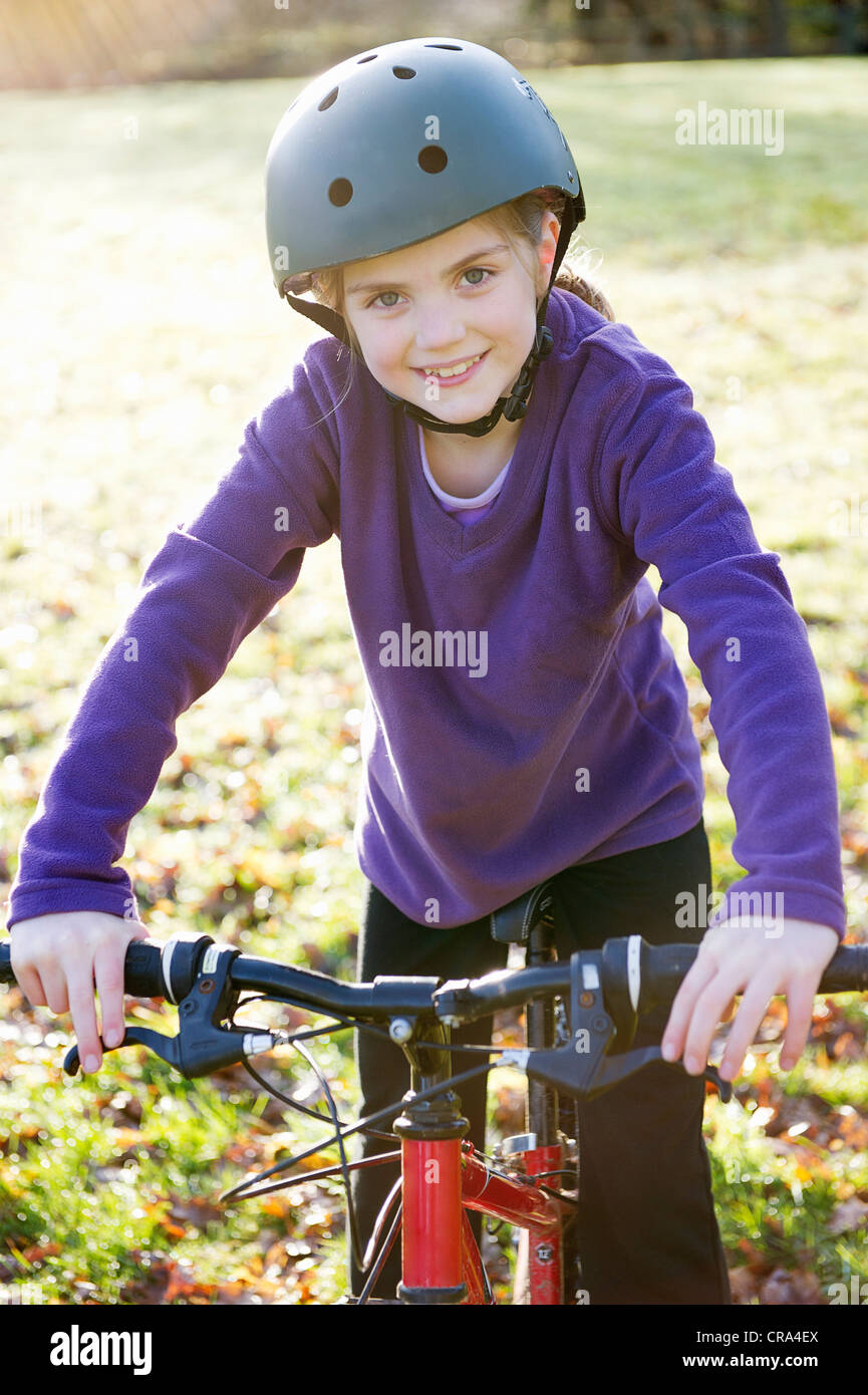 Girl riding bicycle in meadow - Stock Image