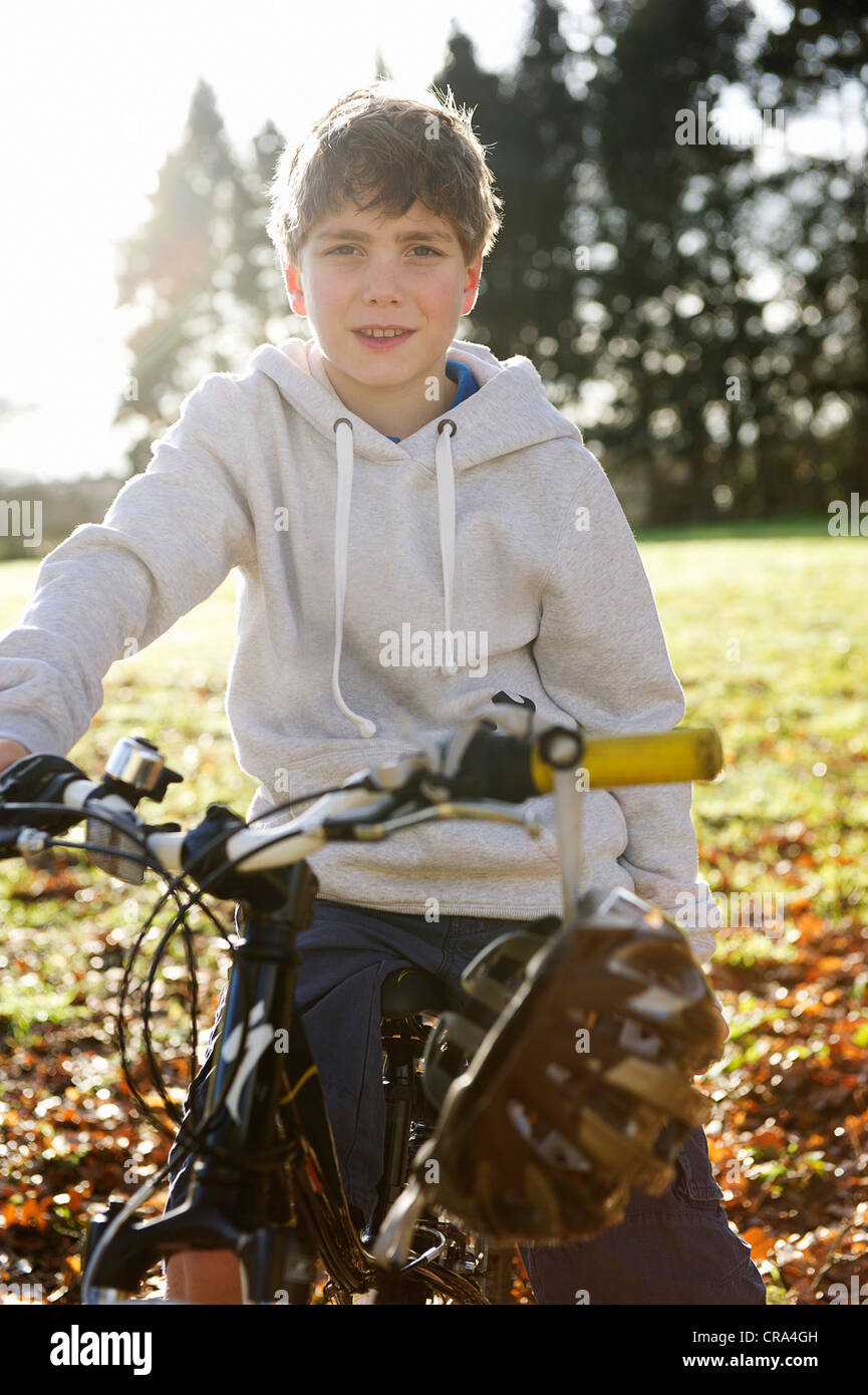 Boy riding bicycle in meadow - Stock Image